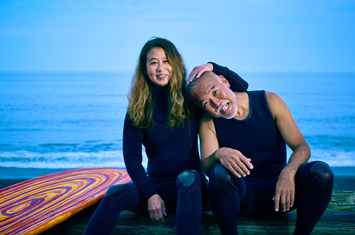 Senior couple sit on the sea sand before surfing early in the morning next to surfboard - gettyimageskorea