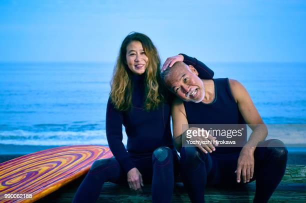 senior couple sit on the sea sand before surfing early in the morning next to surfboard - beautiful dominant women stock pictures, royalty-free photos & images