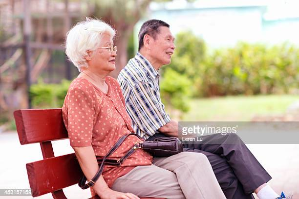 Senior couple sit together in park