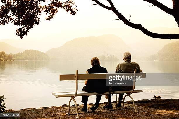 altes paar auf bank zum sitzen am lake shore - seeufer stock-fotos und bilder
