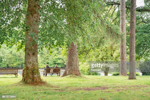 Senior couple sits on bench at River Tay in Dunkeld Scotland UK