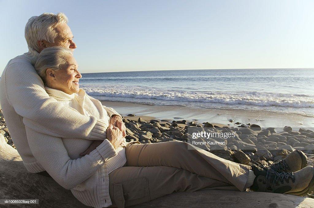 Senior couple sitting at beach, smiling : Foto stock