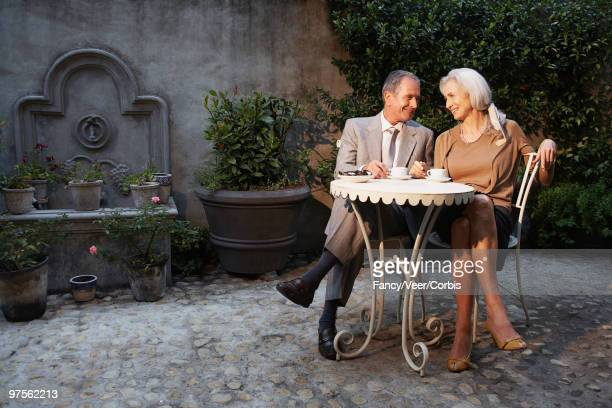 Senior couple sitting at table in courtyard patio