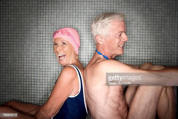 Senior couple sitting back to back, close-up