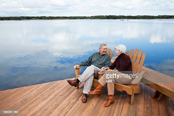 senior couple sitting by water - pier stock pictures, royalty-free photos & images