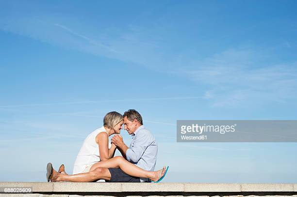 Senior couple sitting head to head on a wall in front of the city