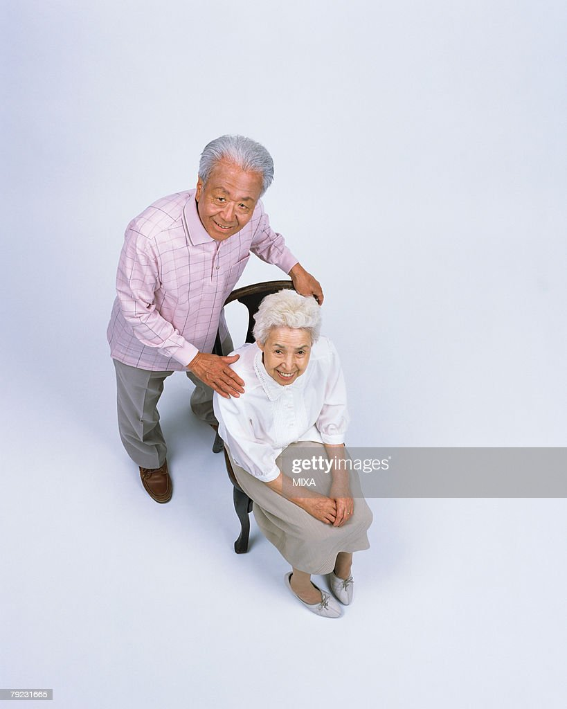 A senior couple sitting in a chair : Stock Photo