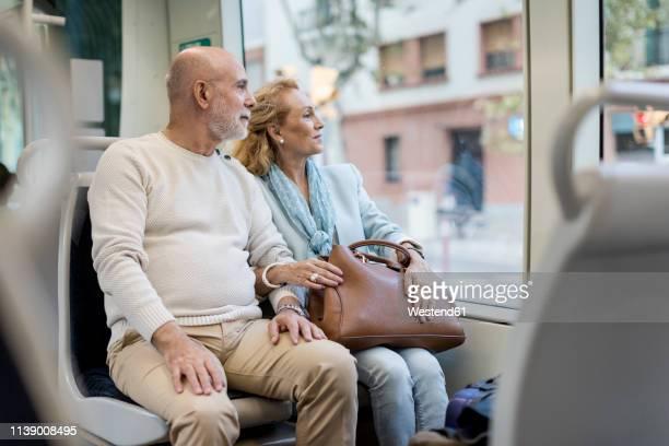 senior couple sitting in a tram - öffentliches verkehrsmittel stock-fotos und bilder