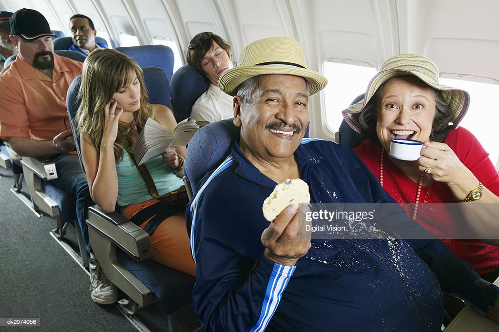 Senior Couple Sitting in an Aircraft Cabin Eating and Drinking and Passengers Behind : Stock Photo