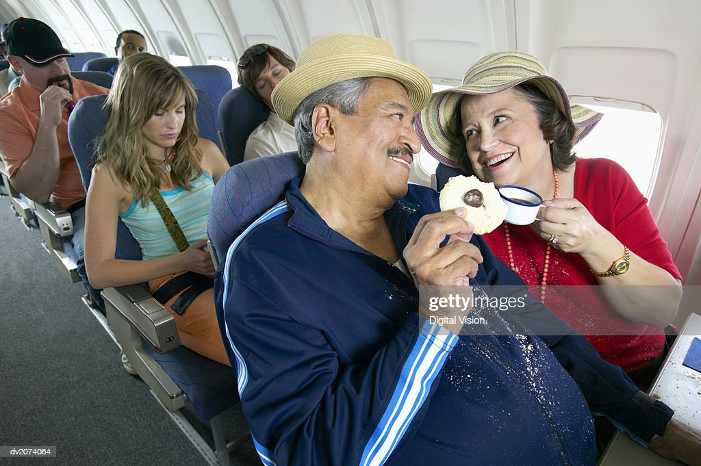 Senior Couple Sitting in an Aircraft Cabin Eating and Drinking : Stock Photo