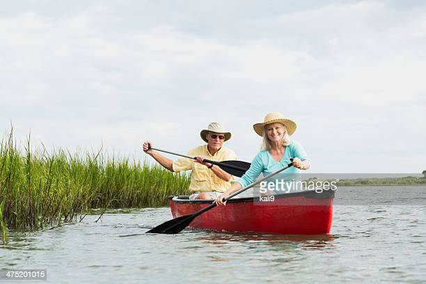 Senior couple sitting in canoe, paddling with oars