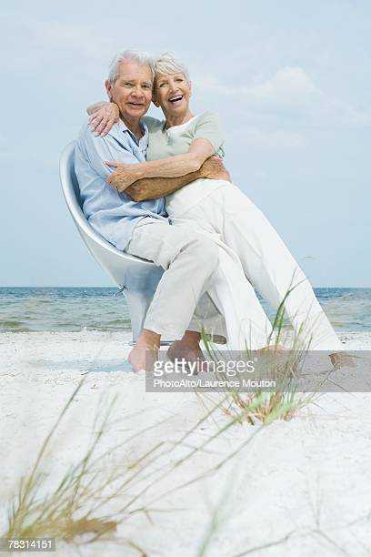 Senior couple sitting in chair together on beach, embracing, woman sitting on man's lap, both smiling at camera