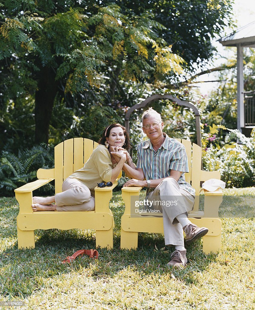 Senior Couple Sitting in Chairs Holding Hands on Their Garden Lawn : Stock Photo