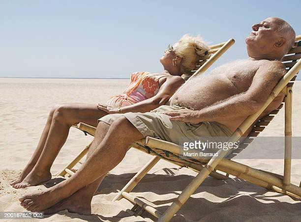 senior couple sitting in chairs on beach, eyes closed - fat man on beach stock photos and pictures