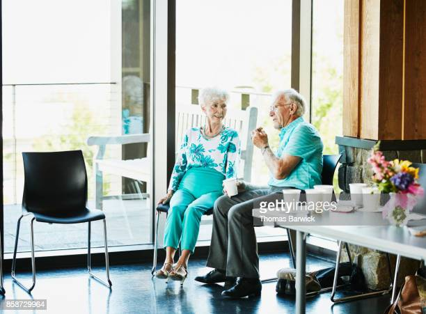 Senior couple sitting in community center relaxing during dance