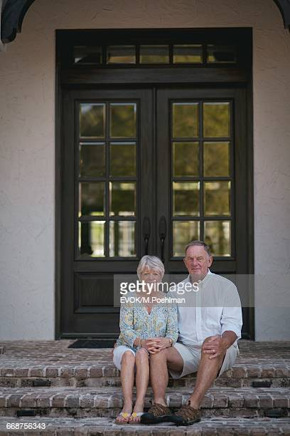 Senior couple sitting in front of house