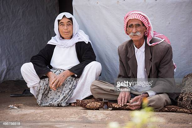 Senior couple sitting in front of their tent