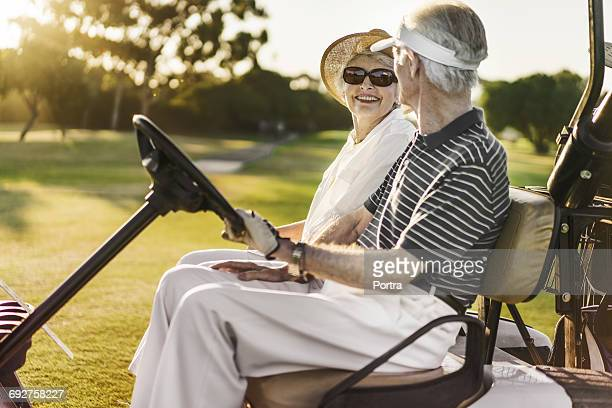 Senior couple sitting in golf cart at golf course