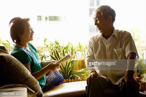 Senior couple sitting in living room, woman holding book
