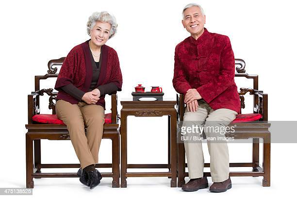 Senior couple sitting in Ming style chair