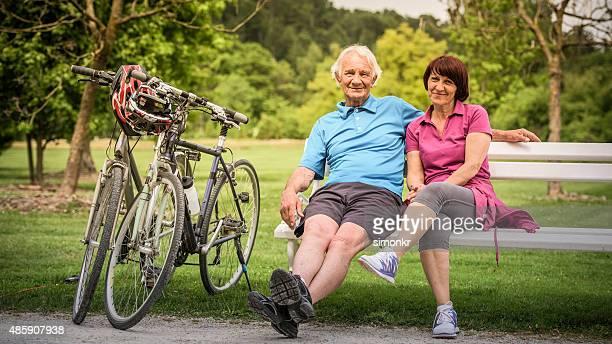 altes paar sitzen im park neben fahrrädern - pedalantrieb stock-fotos und bilder