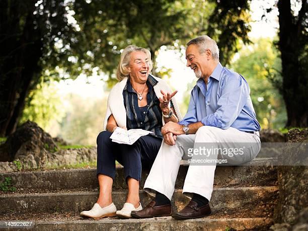 Altes Paar Sitzen im Park Holding Karte