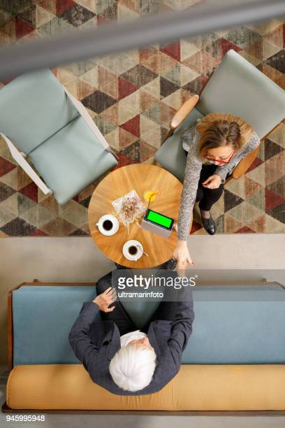 Senior couple sitting in retro hotel drink coffee and chatting. Active seniors, using digital tablet and smartphone, browsing the internet.  Directly above.