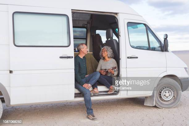 Senior couple sitting in their camping van in the desert