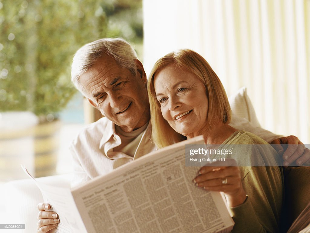 Senior Couple Sitting Indoors Together Reading a Newspaper : Stock Photo