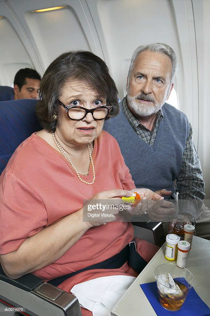 Senior Couple Sitting Inside a Plane, Woman Anxiously Taking Tranquilizers : Stock Photo