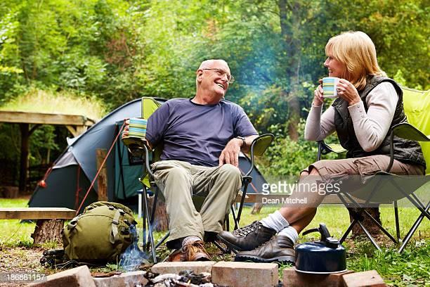 Couple âgé assis près d'un feu de camp