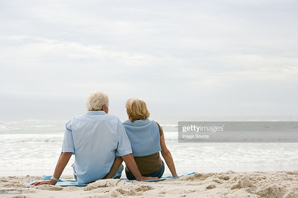Senior couple sitting on a beach : Stock Photo