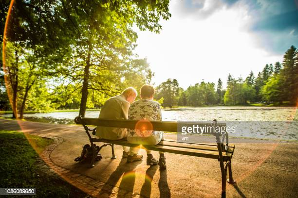 senior couple sitting on a bench next to a lake in a park - bench stock pictures, royalty-free photos & images