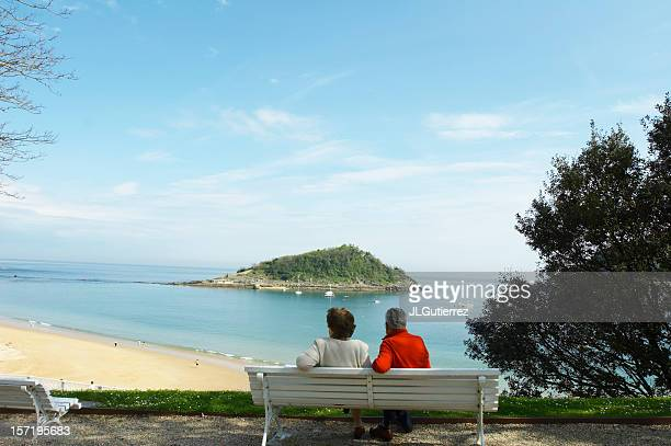 A senior couple sitting on a bench overlooking a beach