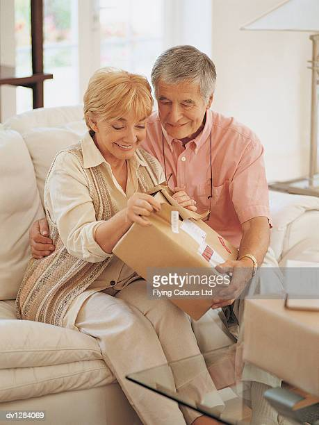Senior Couple Sitting on a Sofa at Home and Opening a Parcel