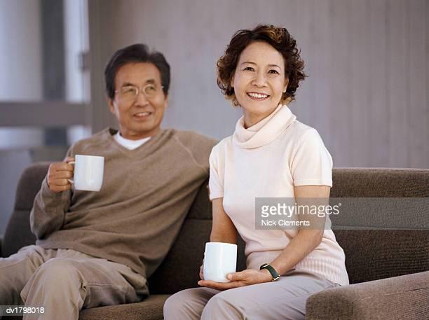 Senior Couple Sitting on a Sofa Holding Mugs