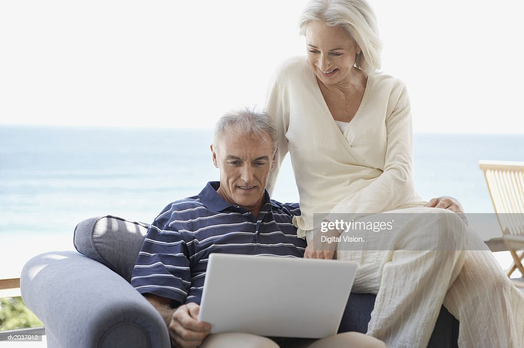 Senior Couple Sitting on an Arm Chair and Looking at a Laptop Computer : Stock Photo