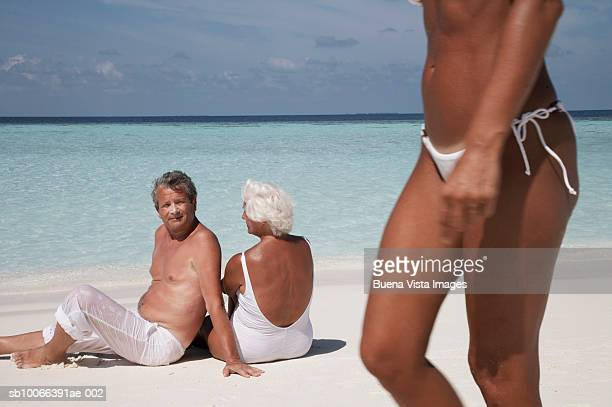 Senior couple sitting on beach, man looking at woman walking on beach