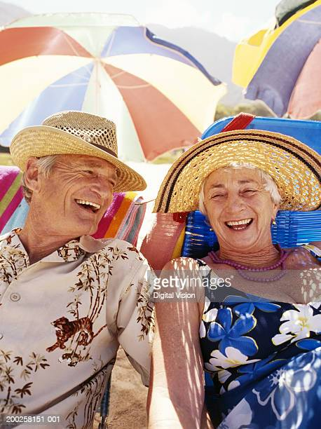 Senior couple sitting on beach under umbrella, laughing