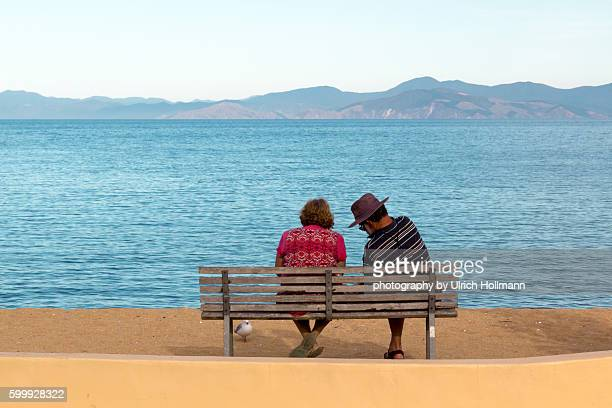 Senior couple sitting on bench at waterfront