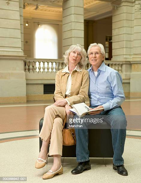 Senior couple sitting on bench in museum concourse, man holding book