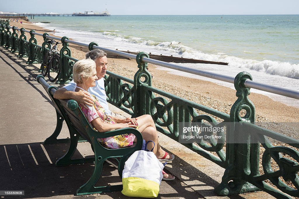Senior couple sitting on bench looking at sea. : Stock-Foto