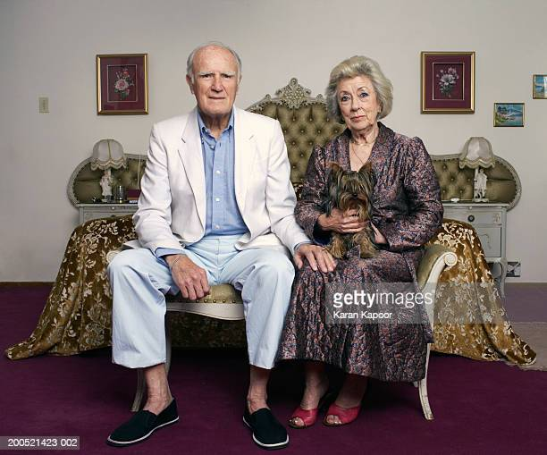 senior couple sitting on chair in bedroom, with dog, portrait - side by side stock pictures, royalty-free photos & images