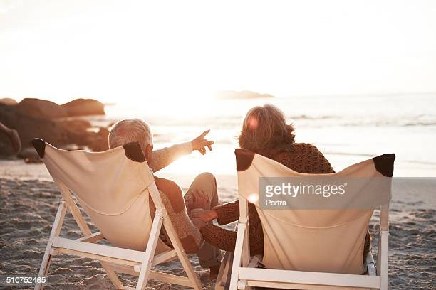 senior couple sitting on chairs at beach - outdoor chair stock pictures, royalty-free photos & images