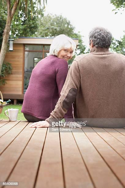 Senior couple sitting on deck in backyard
