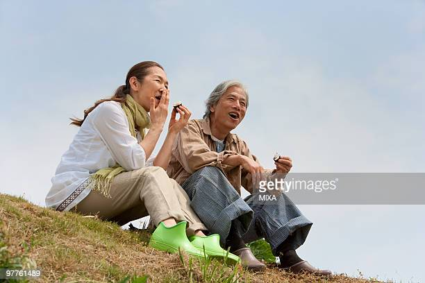 senior couple sitting on field - rice ball stock pictures, royalty-free photos & images
