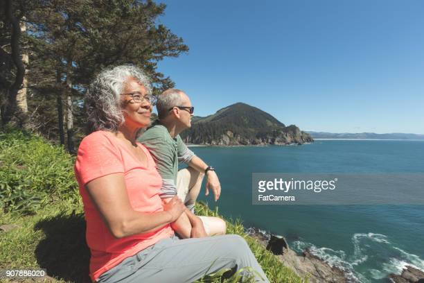 senior couple sitting on grassy bluff overlooking ocean - oregon coast stock pictures, royalty-free photos & images