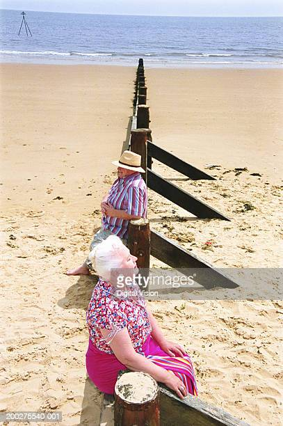 Senior couple sitting on groynes in opposite directions, elevated view
