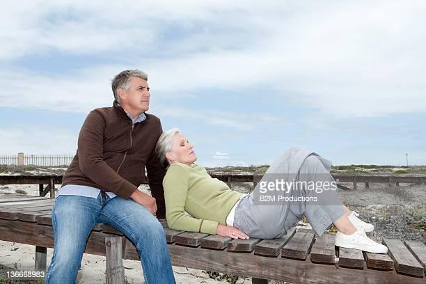 Senior Couple Sitting On Jetty At Beach