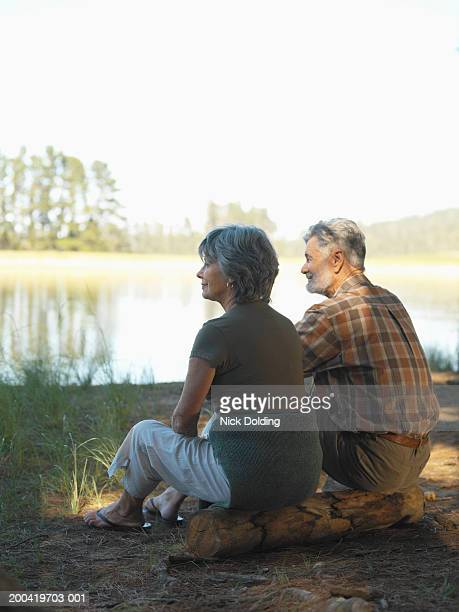 Senior couple sitting on log facing lake, smiling, rear view